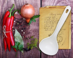 Spices and old recipe book on wooden background.