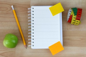 A blank notebook, green apple, pencil, measuring tape on wooden